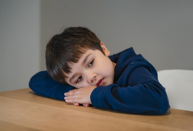 Portrait tired kid lying head down on his arm lookig out deep in throught