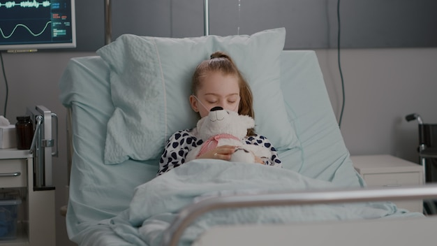 Portrait of tired sick child sleeping after suffering medical recovery surgery during disease examination in hospital ward. hospitalized kid resting in bed wearing oxygen nasal tube