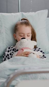 Portrait of tired sick child sleeping after suffering medical recovery surgery