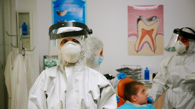 Portrait of tired stomatologist woman with coverall and face shield looking at camera sitting in new normal dental office. pediatric nurse talking with child patient in background.
