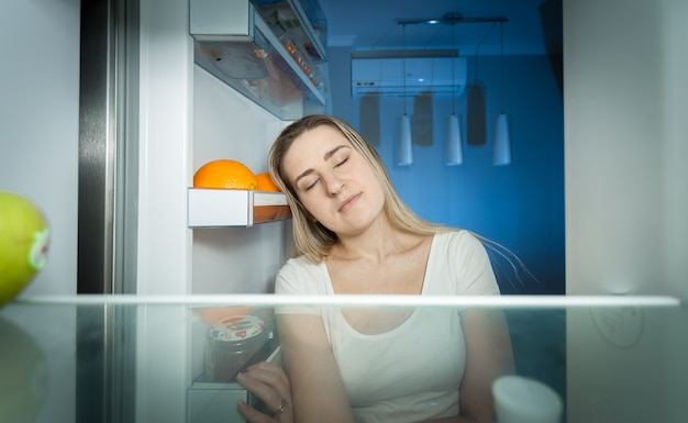 Portrait of tired woman in pajamas looking inside of refrigerator at late night