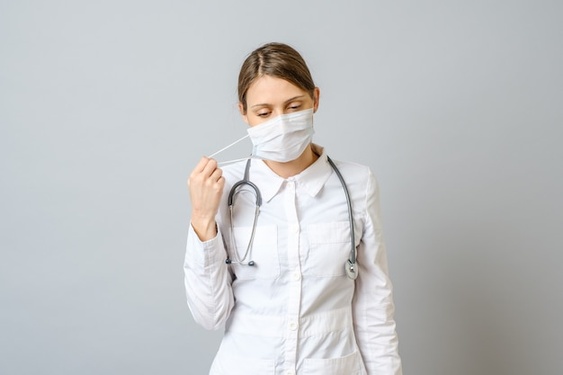 Portrait of tired young doctor taking off medical face mask isolated over gray wall