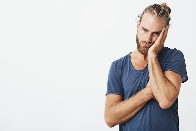 Portrait of tired young man with stylish hairstyle and beard