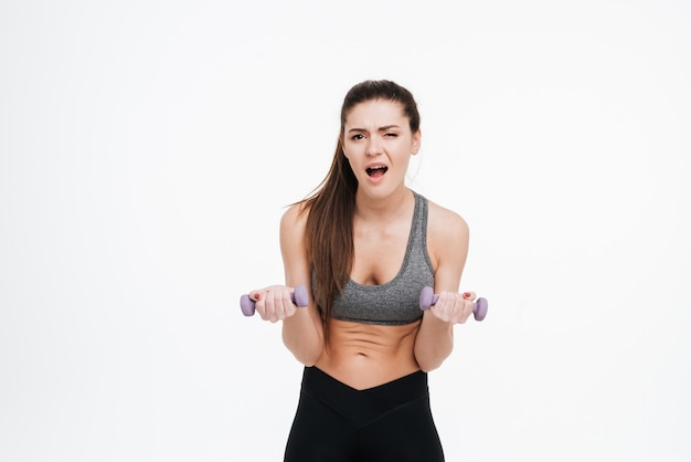 Portrait of a tired young sportswoman doing intensive training with dumbbells isolated