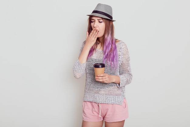 Portrait of tired young woman wearing hat, having bright violet hair, holding disposable cup with coffee, needs energy to wake up, isolated over grey background.
