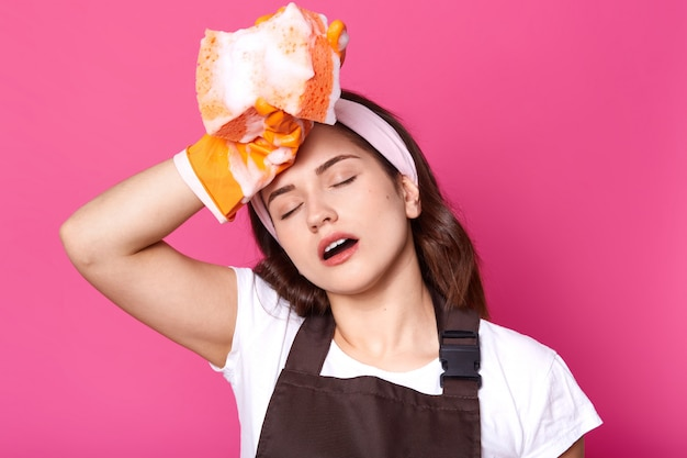 Portrait of tired young woman with orange sponge in hand, cleans her house wearing orange rubber gloves for hands protection, brown apron, t shirt and handband, stands with closed eyes and open mouth.