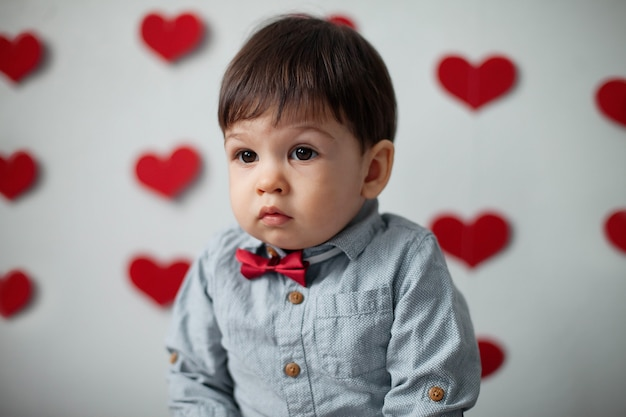 Portrait of a toddler boy in a shirt with a bow tie on a wall background with hearts on valentine's day.