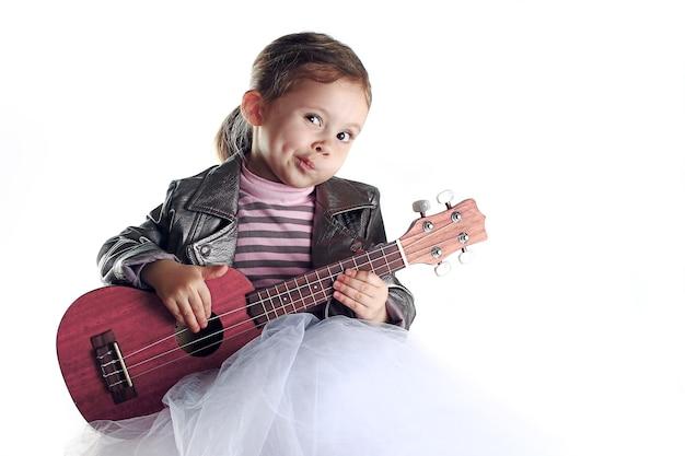 A portrait of toddler girl with ukulele on white background.