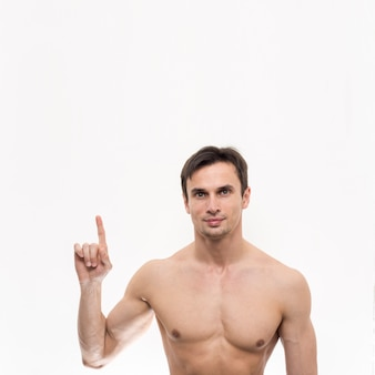 Portrait of topless man pointing up