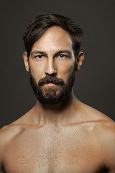 Portrait of topless serious man with beard and mustache looking straight severe.