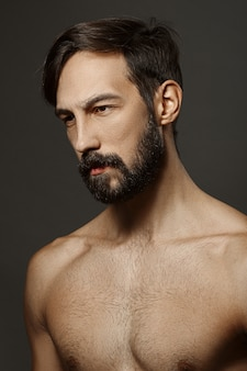 Portrait of topless serious man with beard and mustache