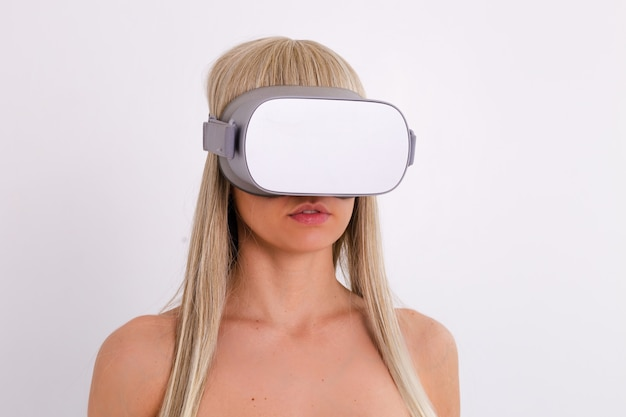 Portrait of topless woman in virtual reality glasses, studio shot, white.