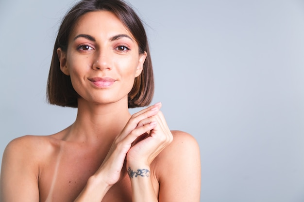 Portrait of topless woman with makeup and soft gentle tanned skin on gray wall