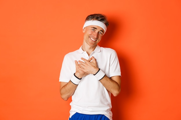 Portrait of touched and grateful adult man in sportswear, thanking and looking pleased