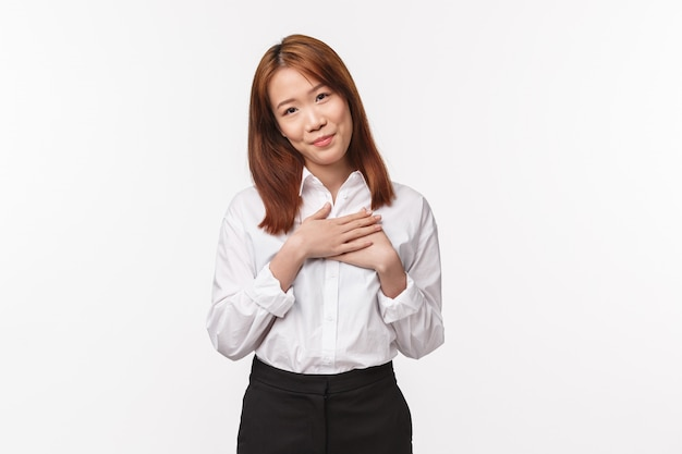 Portrait of touched and grateful charming asian elegant woman, touching heart and sighing happy, smiling tilt head looking with love and care, thanking for praises and warm compliments