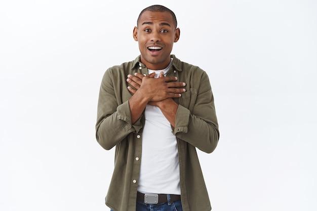 Ritratto di un uomo afroamericano commosso e felice che sospira e tocca il cuore mentre ascolta notizie piacevoli