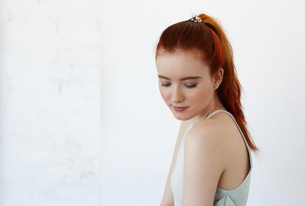 Ritratto di toccare la giovane donna allo zenzero con bel viso guarda in basso con espressione timida o civettuola in piedi isolato