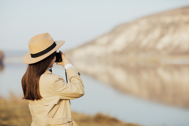 Portrait of tourist girl in hat and trench coat takes picture on retro camera during travel in mountain.