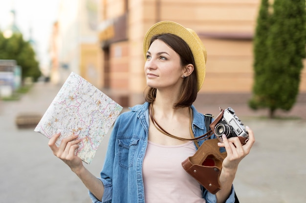 Portrait of tourist holding camera and local map