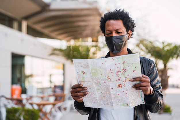 Portrait of tourist man wearing protective mask and looking for directions on map while walking outdoors on the street