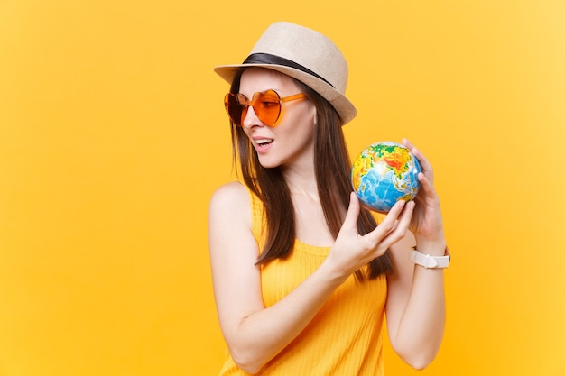 Portrait of tourist woman in summer hat, orange glasses hold in hands globe isolated on yellow background. traveling abroad to travel weekends getaway. air flight journey concept. stop nature garbage.