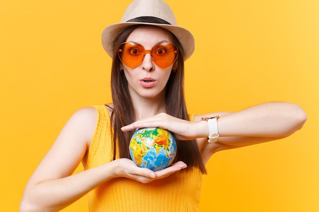 Portrait of tourist woman in summer hat, orange glasses hold in palms globe isolated on yellow background. traveling abroad to travel weekends getaway. air flight journey concept. stop nature garbage.