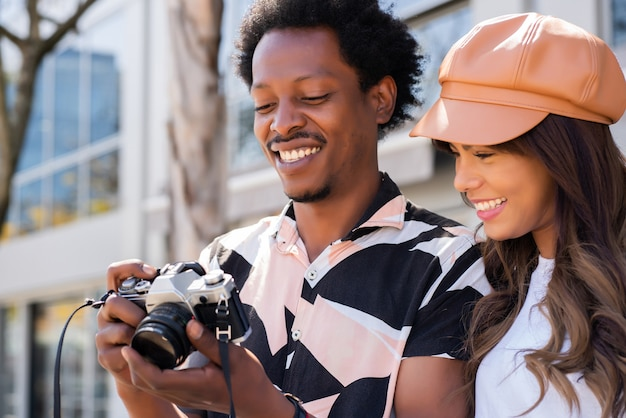 Portrait of tourist young couple using camera and taking photographs in the city. tourism concept.