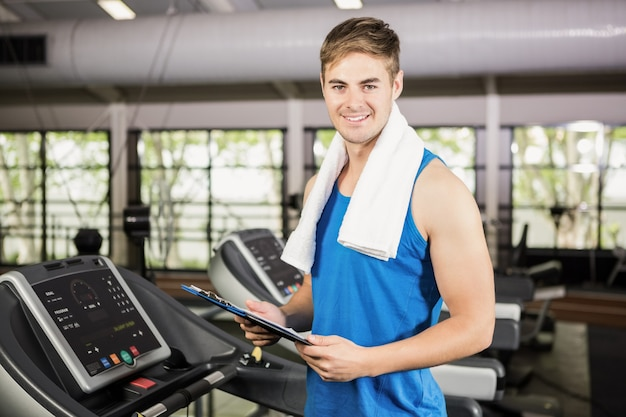 Portrait of trainer holding clipboard on treadmill
