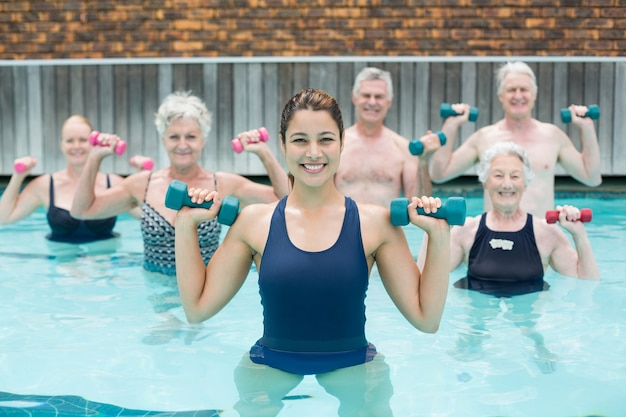 Portrait of trainer with senior swimmers exercising in swimming pool