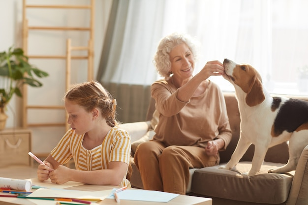 Portrait of tranquil family scene with senior woman playing with dog and cute red haired girl drawing pictures beside her in cozy home interior