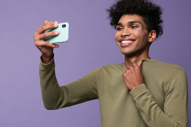 Portrait of transgender latino male taking selfies with mobile in hand happy trans gender young man
