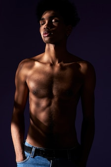 Portrait of transgender model with closed eyes stand in casual pose in shadow muscular trans gender