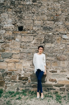 Portrait of traveler girl in white dress stands at ancient stone wall