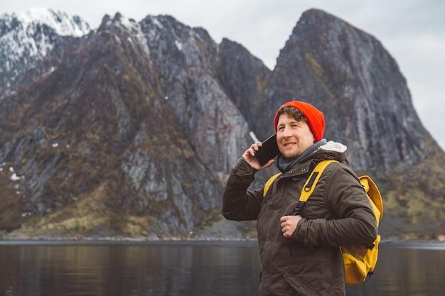 세로 여행자 남자 휴대 전화에 대 한 얘기입니다. 산과 호수를 배경으로 노란색 배낭을 메고 서 있는 관광객. 여행자가 걷고, 웃는 남자가 친구에게 전화를 걸고 있습니다. 전화 대화.