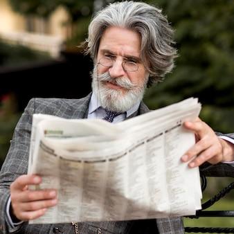 Portrait of trendy mature male reading newspaper