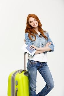 Ritratto di giovane ragazza zenzero alla moda in piedi con la valigia e in possesso di passaporto con biglietti su w...