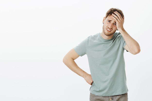 Portrait of troubled gloomy european male model in casual outfit, holding palm on forehead and frowning, touching hip with arm, feeling headache from overworking