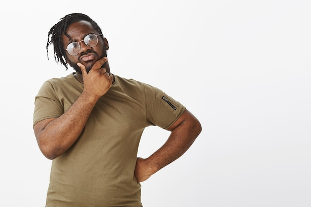 Portrait of troubled guy with glasses posing against the white wall