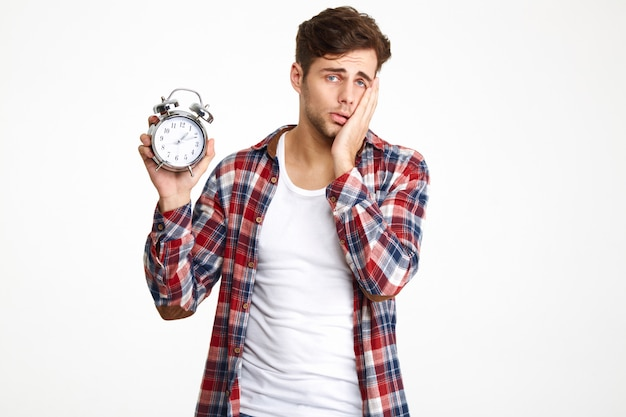 Portrait of a troubled man holding alarm clock