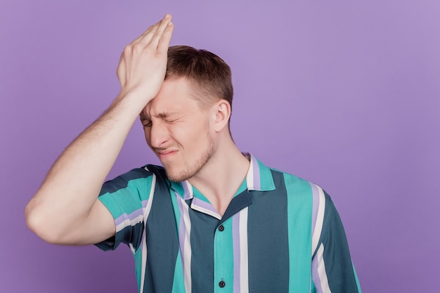 Portrait of troubled stupid guy palm head make mistake failed on purple background