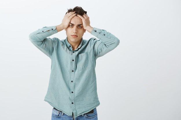 Ritratto di ragazzo europeo stanco turbato in camicia casual