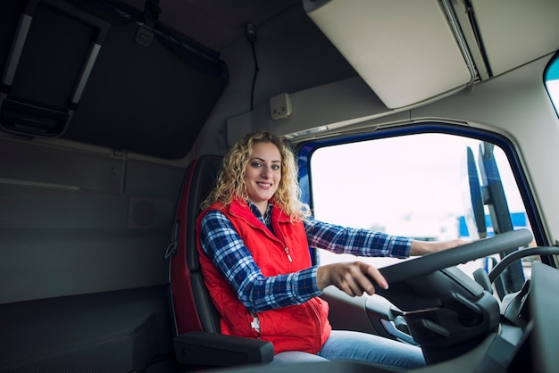 Portrait of trucker sitting in truck cabin with hands on steering wheel
