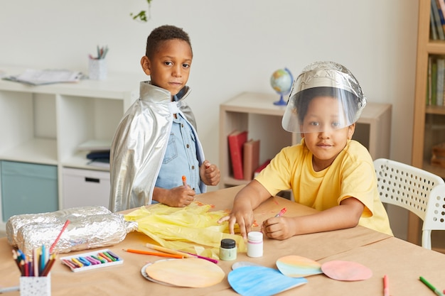 Portrait of two african-american boys playing astronauts while enjoying art and craft lesson in preschool or development center