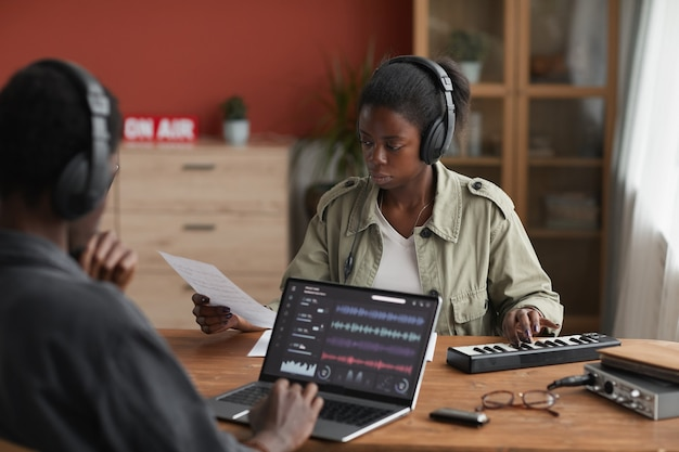 Portrait of two african-american musicians composing music together while sitting at desk in home recording studio, copy space