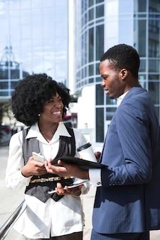 Portrait of two african colleague standing in front of building talking to each other