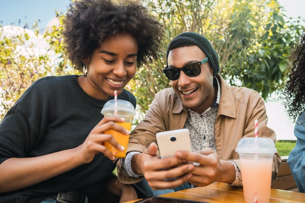 Portrait of two afro friends using their mobile phone at coffee shop. friendship and lifestyle concept.
