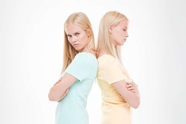 Portrait of two angry ladies standing back to each other with arms crossed isolated over white wall