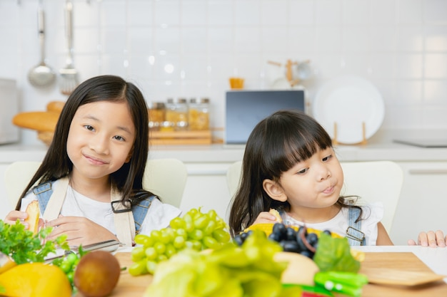 Portrait two asian sister playing and care together eating at home kitchen.