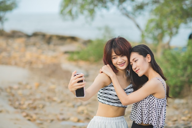 Portrait  of  two asian woman in swimming suit selfie by phone at beach