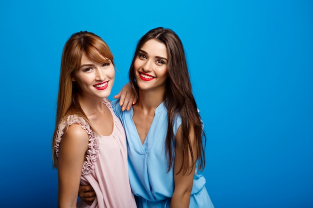 Portrait of two beautiful girls over blue wall